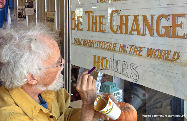 Artist Bill Warren hand paints the lettering on a window at The B.T.C. Old-Fashioned Grocery.